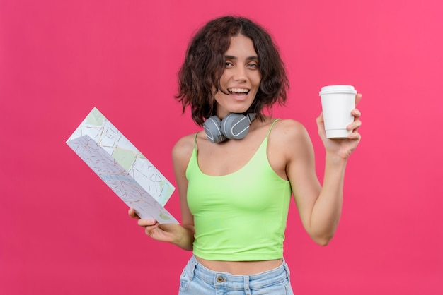 プラスチック製のコーヒーカップを保持しているヘッドフォンで緑のクロップトップの短い髪の陽気な若いきれいな女性 無料写真