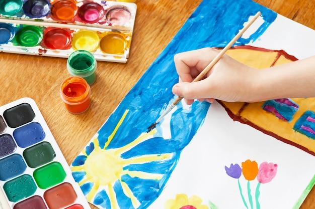 子供はペンキで家と花を描きます。セレクティブフォーカス Premium写真