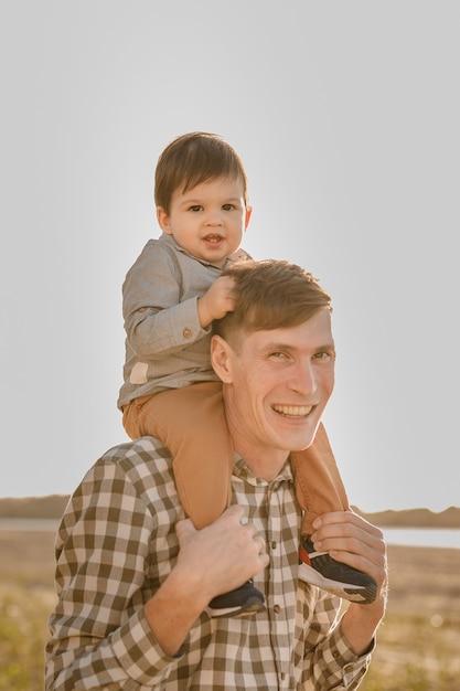 彼の父親の首に子供。水の近くを歩きます。空に対して赤ちゃんとお父さん。 Premium写真