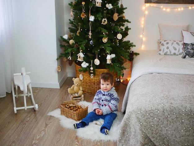 Ребенок на полу возле елки и новогодних украшений Premium Фотографии
