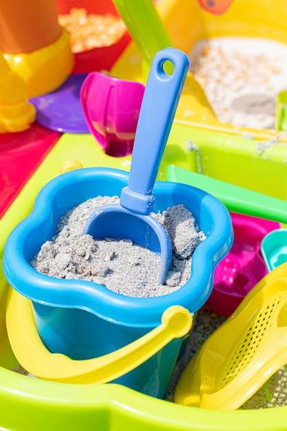 シャベルが砂に詰まった砂でいっぱいの子供のバケツ。 無料写真