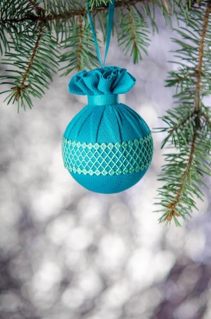 Елочный шар с узором висит на еловой ветке на серебряном фоне. новогоднее украшение. Premium Фотографии