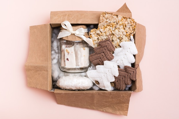 クリスマスプレゼント。ペーストの瓶、シリアルのポテトチップス、ニットのモミの木が入った箱。手工芸品の装飾。ゼロウェイスト Premium写真