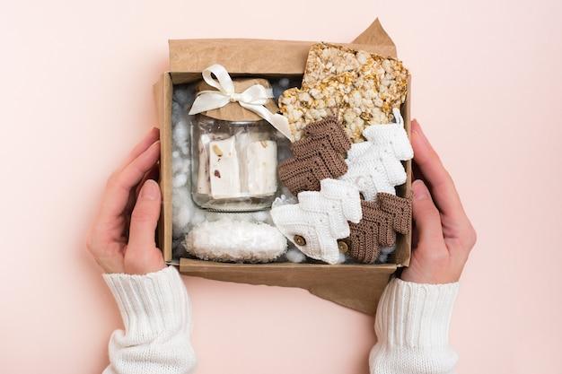 クリスマスプレゼント。女性の手は、ペーストの瓶、シリアルのポテトチップス、ニットのモミの木が入った箱を持っています。手工芸品の装飾。ゼロウェイスト Premium写真