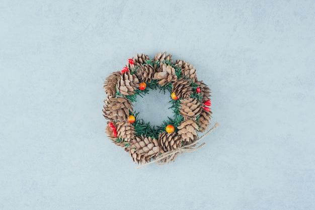 大理石の背景に松ぼっくりからのクリスマスリース。高品質の写真 無料写真