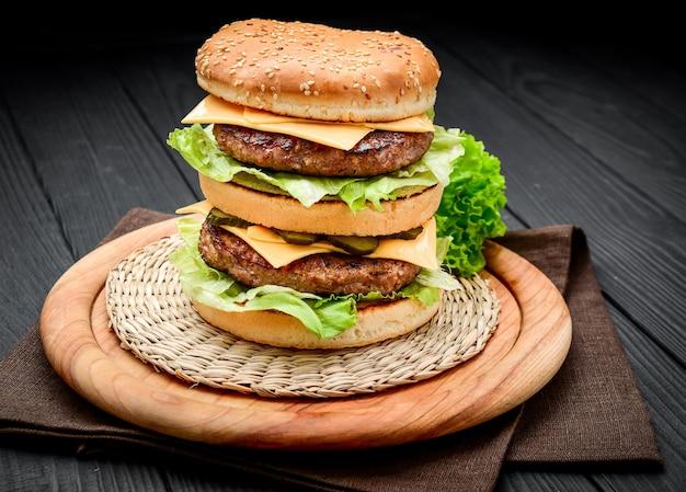 Двойной чизбургер в классическом стиле с двумя котлетами из говядины, соусом, листьями салата, сыром, солеными огурцами и луком на булочке с кунжутом Premium Фотографии