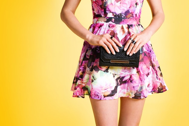 黒い財布を保持しているピンクの花のドレスを着た若いエレガントな女性のクローズアップ 無料写真