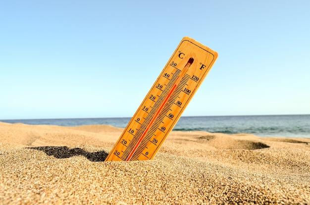 Снимок термометра на песчаном пляже крупным планом Бесплатные Фотографии
