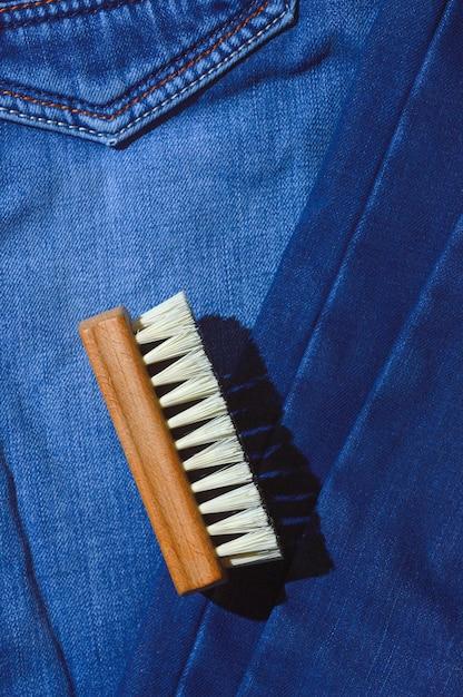 服のブラシは折りたたまれたジーンズの上にあります。 Premium写真