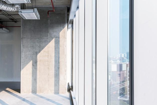 オープンシーリングシステムの工事中の内装改修時に太陽光が当たるコンクリート柱。開発者の投資のための空のスペース。 Premium写真