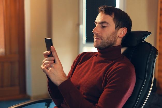 Уверенный в себе мужчина проверяет новости по телефону, сидя в кожаном кресле в офисе Premium Фотографии