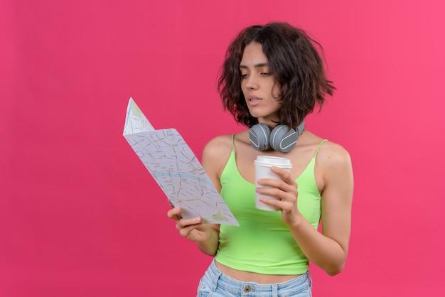 地図を見てコーヒーのプラスチックカップを保持しているヘッドフォンで緑のクロップトップの短い髪の自信を持って若いきれいな女性 無料写真