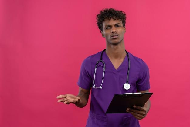 Смущенный молодой красивый темнокожий доктор с вьющимися волосами в фиолетовой форме со стетоскопом сердито смотрит в камеру, держа в руках буфер обмена Бесплатные Фотографии