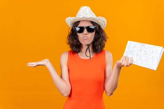 Смущенная молодая женщина с короткими волосами, в оранжевой рубашке, в шляпе от солнца и солнечных очках, поднимает руки с картой, не зная, что делать Бесплатные Фотографии