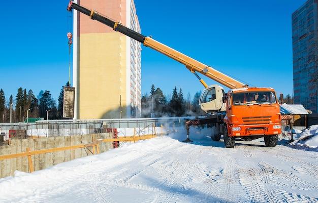 Строительный кран работает на строительной площадке с грузом Premium Фотографии