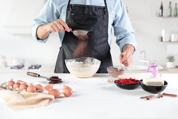 素朴なキッチンで料理人。小麦粉製品や生地、パン、マフィン、パイ、ケーキ、ピザを調理するための食材を使った男性の手 無料写真