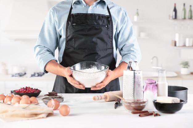 Повар с яйцами на деревенской кухне против мужских рук Бесплатные Фотографии