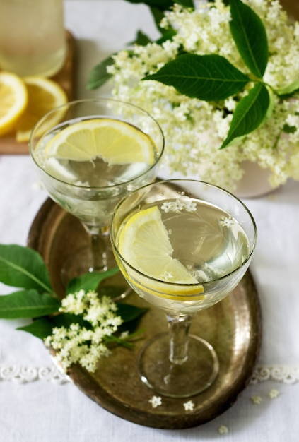 金属製のトレイにグラスにレモンとニワトコの花シロップを入れた冷たい飲み物。素朴なスタイル。 Premium写真
