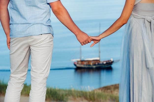 Влюбленная пара стоит на пляже в дюнах на фоне балтийского моря и корабля Premium Фотографии
