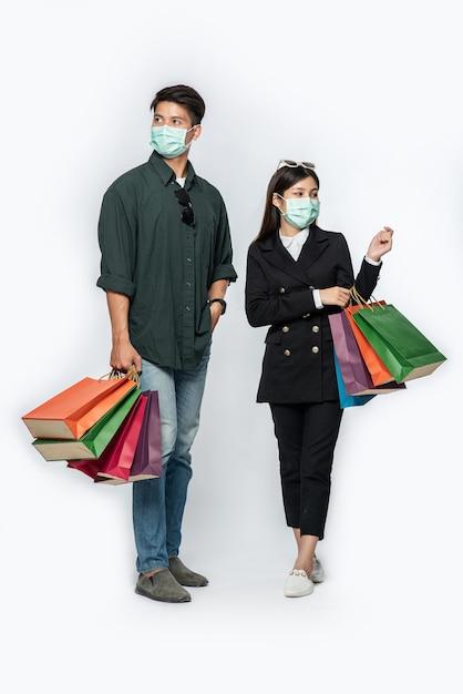 Пара мужчина и женщина в масках несли много бумажных пакетов в магазин Бесплатные Фотографии