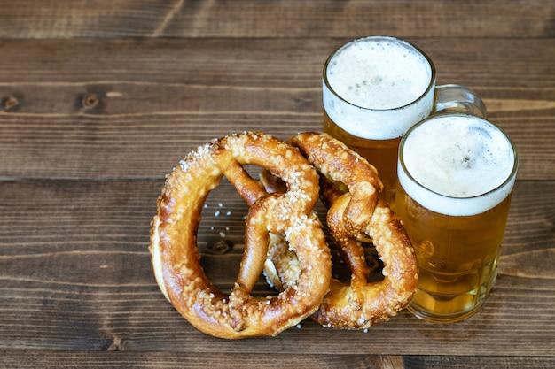 軽いビールとプレッツェルを木製のマグカップのカップル Premium写真