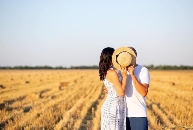 Пара из двух влюбленных стоят на поле, целуются в соломенной шляпе Premium Фотографии