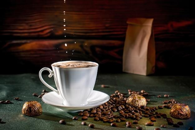Уютный завтрак из клубничного торта, ароматного горячего кофе и шоколадных конфет. на зеленой скатерти на столе от крафт-пакета проснулись кофейные зерна. Premium Фотографии