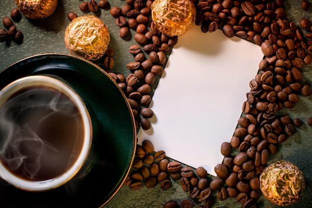 テーブルの上の黒のホットアロマコーヒー、チョコレート、背景の周りに散らばっているコーヒー豆のカップ Premium写真