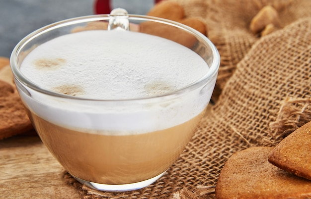 黄麻布にハートの形をしたカプチーノコーヒーとジンジャーブレッドクッキーのカップ Premium写真
