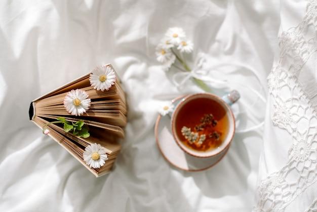 一杯のコーヒーと白いオープンベッドで開いた本。トップビュー。朝の朝食。明るく居心地の良い日 Premium写真