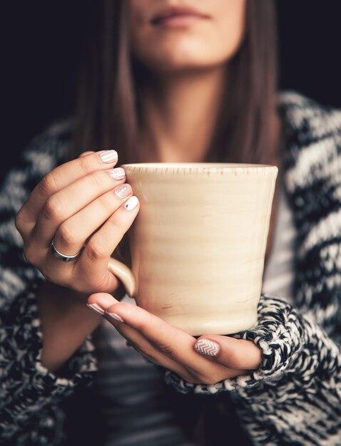 美しい女性の手と美しい唇に一杯のコーヒー Premium写真