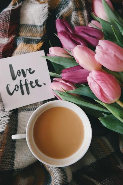 チューリップとグリーティングカードと一緒に格子縞格子縞のコーヒーカップ Premium写真