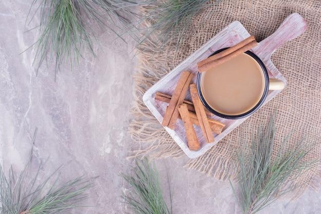 Чашка кофе с палочками корицы на деревенской деревянной доске. Бесплатные Фотографии