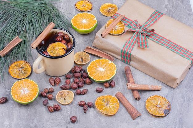 オレンジ、ヒップ、シナモンのグリントワインのカップ 無料写真