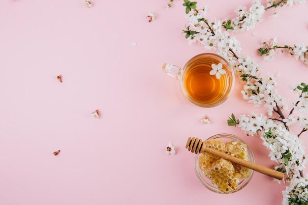 Чашка травяного чая и банка меда на розовом фоне Premium Фотографии