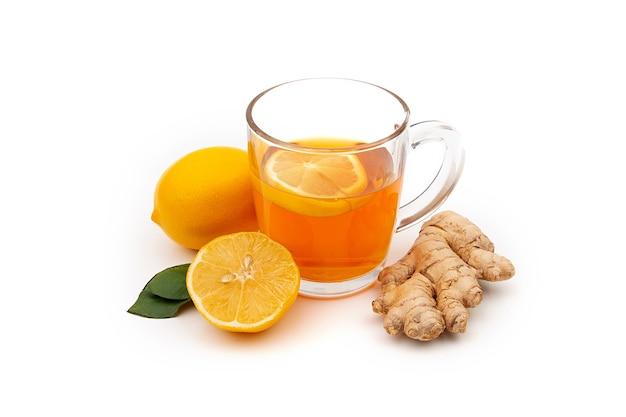 白地にレモンと生姜と熱い黒または緑茶のカップ。インフルエンザやウイルスに対する成分。 Premium写真