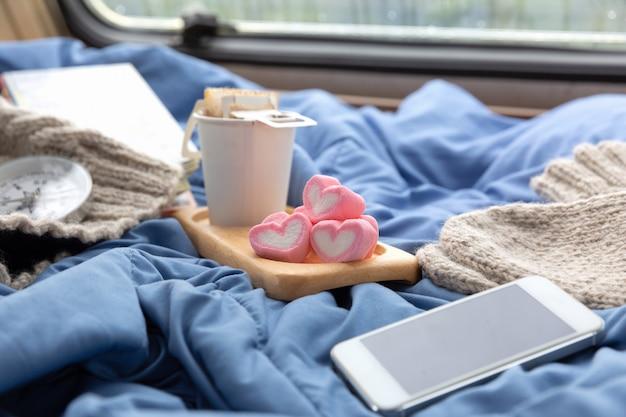 キャラバンの窓の近くにマシュマロとホットコーヒーのカップ 無料写真