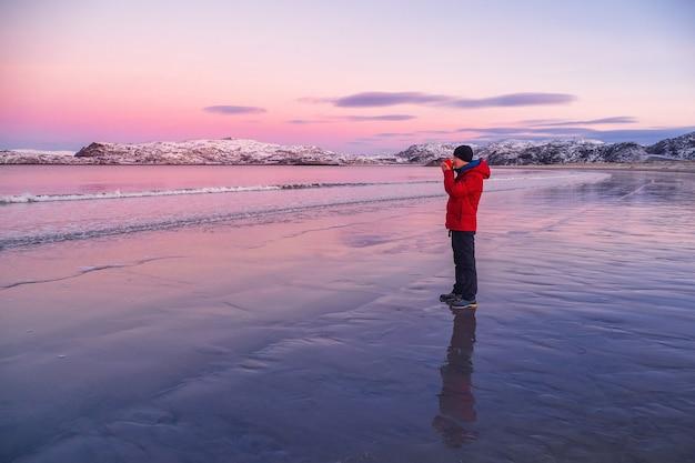 눈 덮인 북부 언덕을 배경으로 북극 해안에있는 한 남자의 손에 따뜻한 차 한잔. 멋진 극지 일몰. 여행 개념. 프리미엄 사진