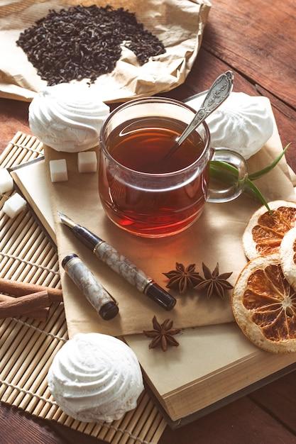 熱いお茶、スパイス、お菓子、木製のテーブルの上にペンで封筒 Premium写真