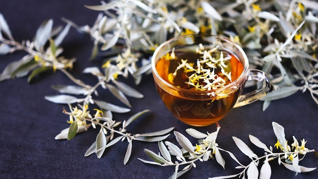海クロウメモドキのお茶。お茶の海クロウメモドキの花。海クロウメモドキの葉とお茶。若い枝と海クロウメモドキの花。癒しのドリンク。 Premium写真