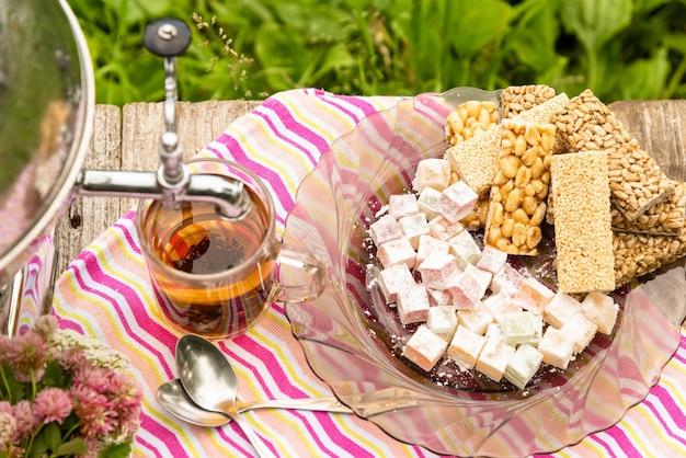 Чашка чая и самовар на деревянном столе со сладостями. Premium Фотографии