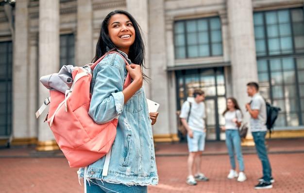 キャンパスの近くの学生のグループの背景にピンクのバックパックとラップトップを持つかわいいアフリカ系アメリカ人の女子学生。 Premium写真