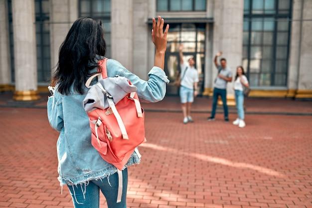 Милая афроамериканская студентка с розовым рюкзаком машет группе студентов возле кампуса. Premium Фотографии
