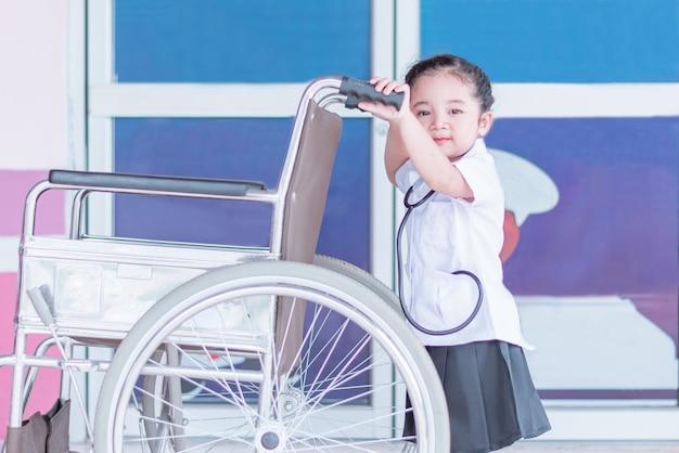 Милая и милая азиатская девочка в униформе медсестры держит инвалидное кресло Premium Фотографии