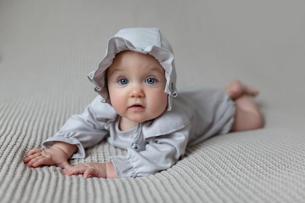Милая маленькая девочка в легком красивом легком боди и кепке на кровати дома Premium Фотографии