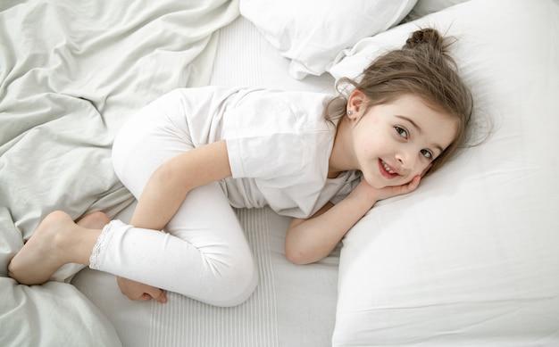 かわいい女の子が白いベッドで寝ています。子供の発達と睡眠の概念。 無料写真
