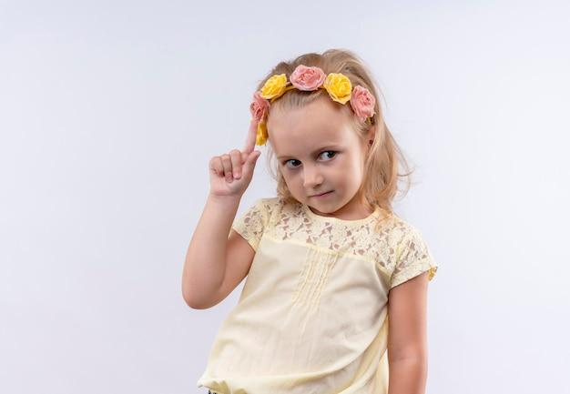 白い壁に人差し指で上向きの花のヘッドバンドで黄色のシャツを着ているかわいい女の子 無料写真