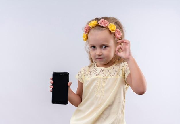 白い壁にokジェスチャーで携帯電話の空白スペースを示す花のヘッドバンドで黄色のシャツを着ているかわいい女の子 無料写真