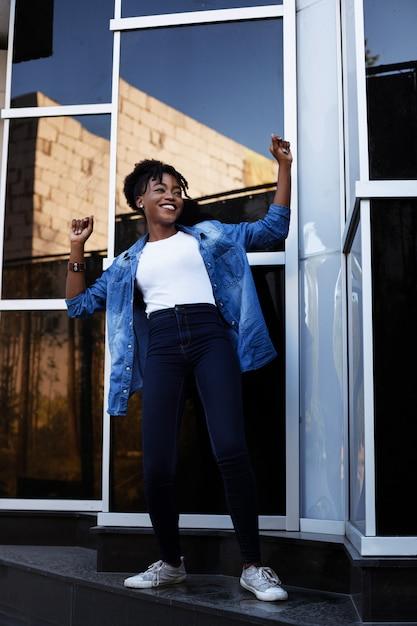 浅黒い肌のアフリカ系アメリカ人の女性は幸せで、夏の街の散歩で踊っています。平等 Premium写真