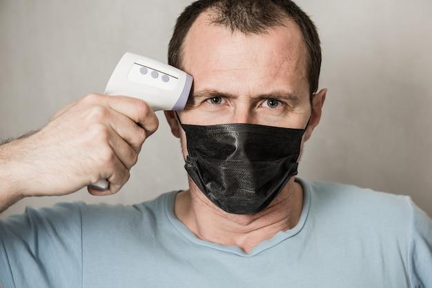 ウイルスの症状-流行性ウイルスの発生の概念の体温を確認するために赤外線額温度計を使用する準備ができて防護マスクを着て落ち込んでいる男コロナウイルス、温度計ガン Premium写真